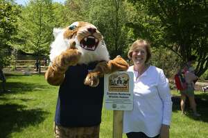 Whitby Librarian and Media and Makerspace Specialist Alexis Ryan next to the Whitby Wildcat after the ribbon cutting commemorating the school's newly certified Audubon Schoolyard Habitat.