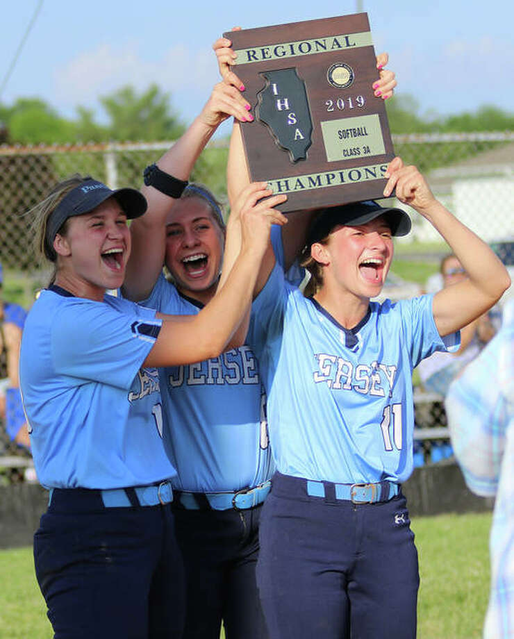 Jersey senior captains (from left) Chelsea Maag, Melissa Weishaupt and Brooke Tuttle deliver the Class 3A regional championship plaque to teammates after beating Columbia 8-1 in the title game at Jerseyville. It is Jersey's first regional title. Photo: Greg Shashack / The Telegraph