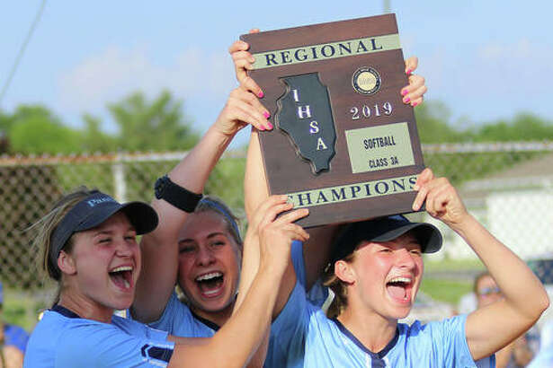 Jersey senior captains (from left) Chelsea Maag, Melissa Weishaupt and Brooke Tuttle deliver the Class 3A regional championship plaque to teammates after beating Columbia 8-1 in the title game at Jerseyville. It is Jersey's first regional title.