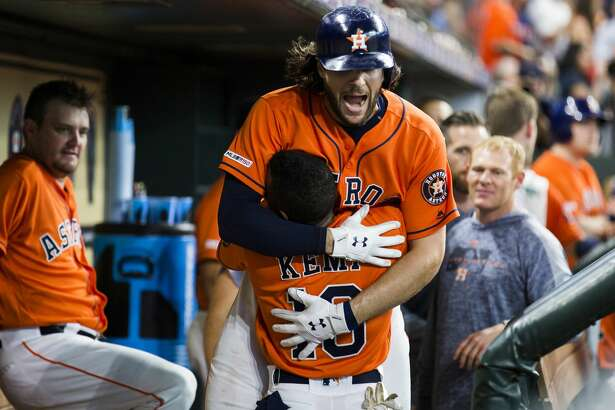 Houston Astros left fielder Tony Kemp (18) picks up Houston Astros center fielder Jake Marisnick (6) after Marisnick scored a homer against the Boston Red Sox during the third inning on Friday, May 24, 2019, in Houston.