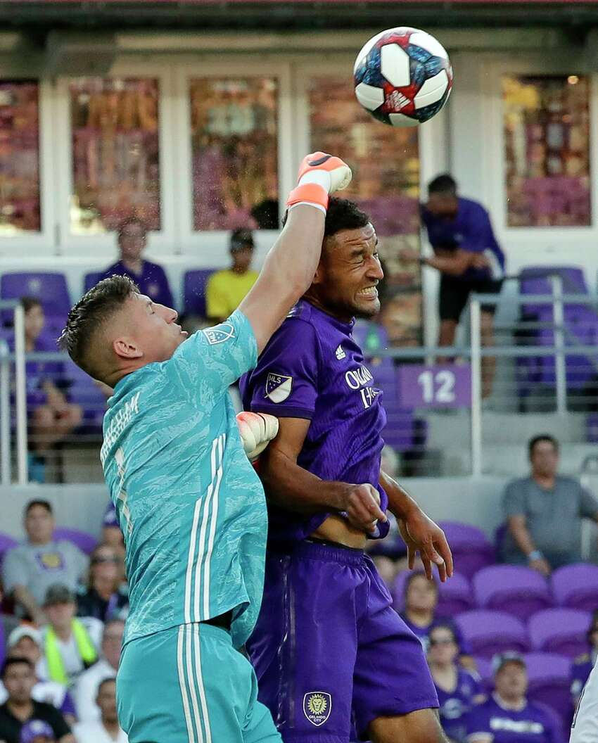 LA Galaxy goalkeeper David Bingham, left, pushes the ball away from Orlando City's Tesho Akindele, who was trying to head the ball to the goal during the first half of an MLS soccer match Friday, May 24, 2019, in Orlando, Fla. (AP Photo/John Raoux)