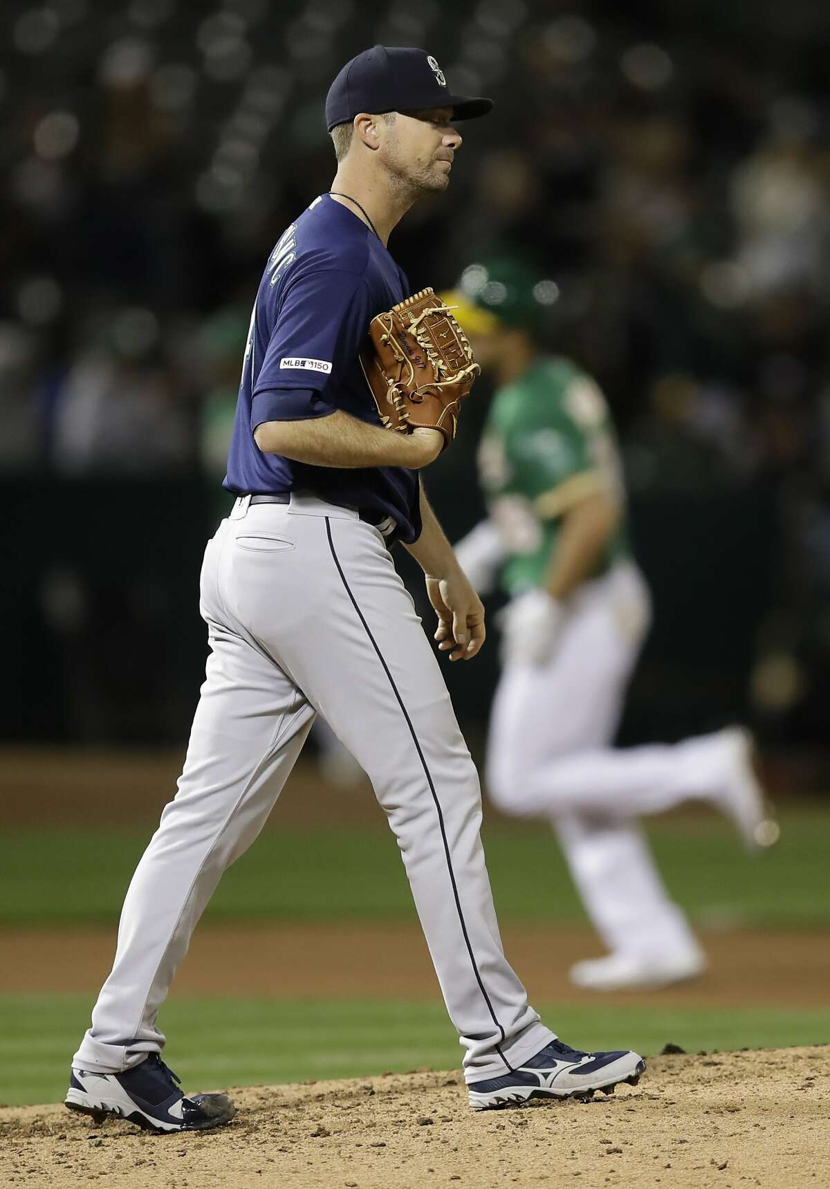 Seattle Mariners' Wade LeBlanc walks back on the mound after giving up a three-run home run to Oakland Athletics' Matt Olson, rear, during the fourth inning of a baseball game Friday, May 24, 2019, in Oakland, Calif. (AP Photo/Ben Margot)