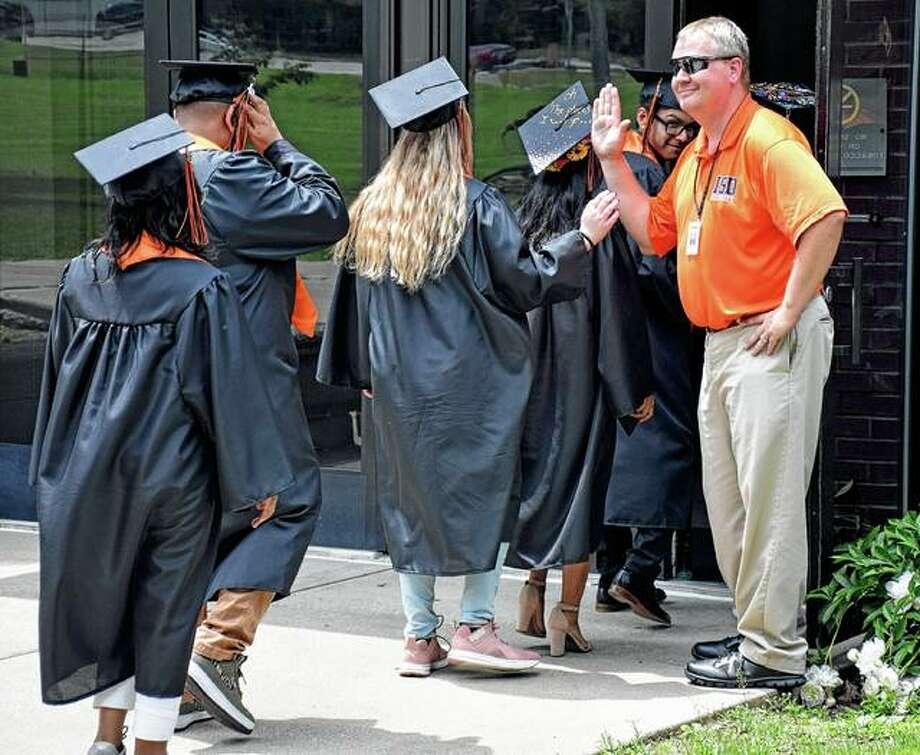 Graduates high-five an ISD staff member as they enter Marshall Gym for their commencement Friday. Photo: David Blanchette | For The Journal-Courier