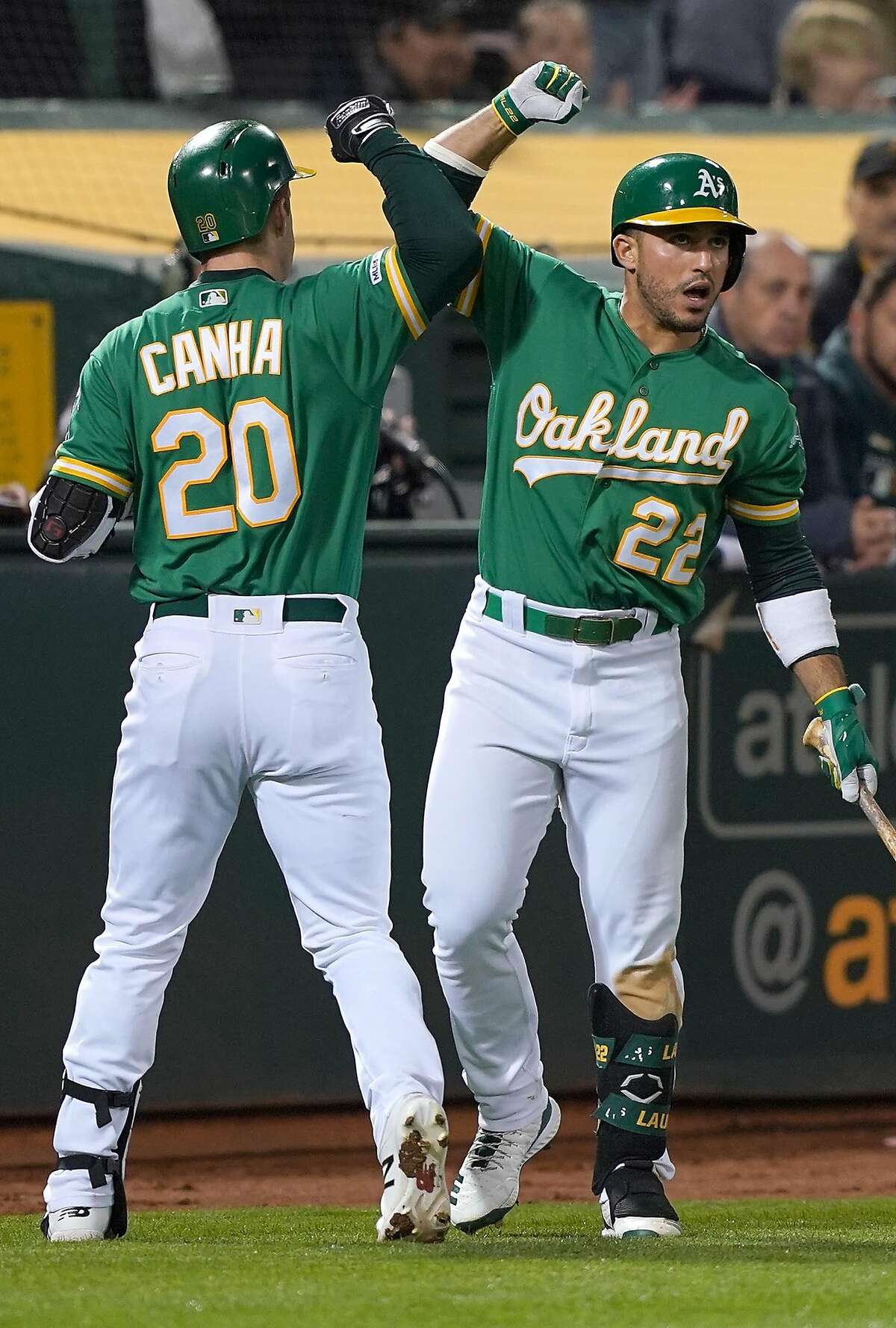 OAKLAND, CA - MAY 24: Mark Canha #20 of the Oakland Athletics is congratulated by Ramon Laureano #22 after Canha hit a solo home run against the Seattle Mariners in the bottom of the fourth inning of a Major League Baseball game at Oakland-Alameda County Coliseum on May 24, 2019 in Oakland, California. (Photo by Thearon W. Henderson/Getty Images)
