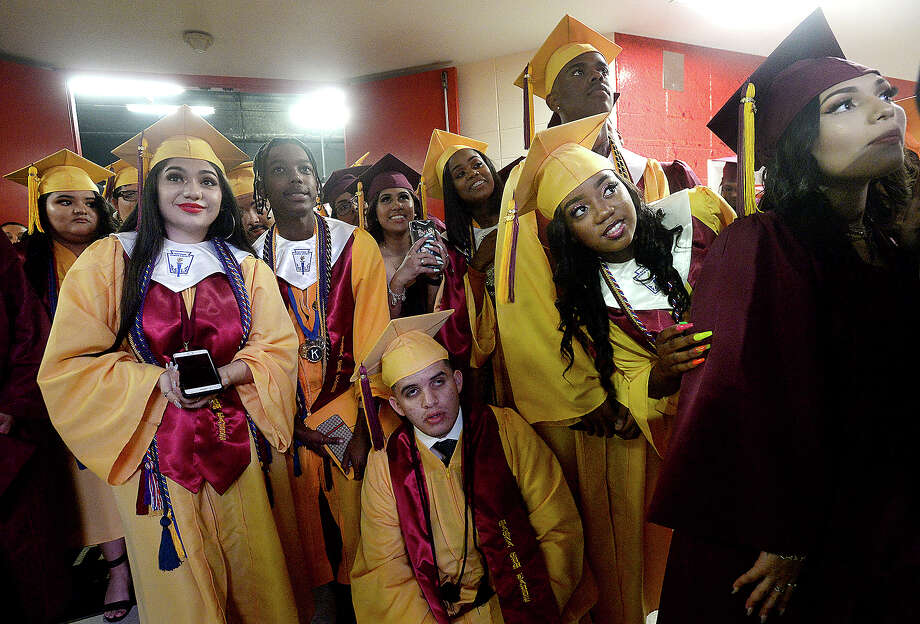 Graduates gather and watch a video playing overhead as they await the start of their entry into the arena during Beaumont United's first commencement ceremony Friday at the Montagne Center.  Photo taken Friday, May 24, 2019 Kim Brent/The Enterprise Photo: Kim Brent/The Enterprise