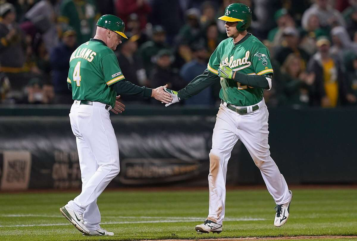 OAKLAND, CA - MAY 24: Stephen Piscotty #25 of the Oakland Athletics is congratulated by third base coach Matt Williams #4 after Piscotty hit a solo home run against the Seattle Mariners in the bottom of the eighth inning of a Major League Baseball game at Oakland-Alameda County Coliseum on May 24, 2019 in Oakland, California. The Athletics won the game 6-2. (Photo by Thearon W. Henderson/Getty Images)