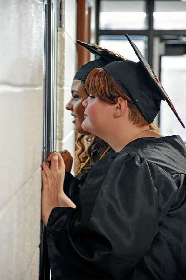 Two Virginia High School seniors sneak a peek at the crowd before Friday's graduation ceremony. Photo: David Blanchette | For The Journal-Courier