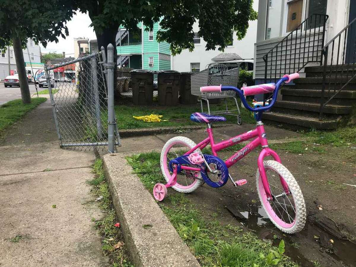 A child's bicycle stands next to discarded police caution tape at a Stamford residence on Frederick Street where a man was killed on Wednesday.