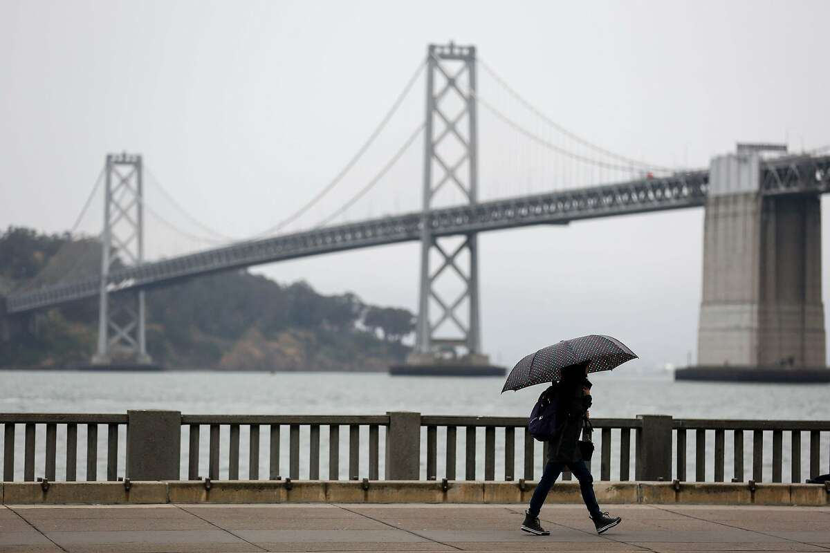 Pedestrians cover up from the rain on Wednesday, May 15, 2019 in San Francisco, Calif.