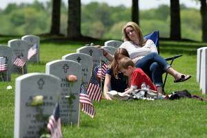 Tara Hulett and her children Savannah, 11, and Ryder, 8, sit next to her father, Navy Veteran Kenneth I. Coons' grave, during the Gerald B.H. Solomon Saratoga National Cemetery 20th Annual Memorial Day Ceremony on Saturday, May 25, 2019 at Saratoga National Cemetery in Schuylerville, NY. (Phoebe Sheehan/Times Union)