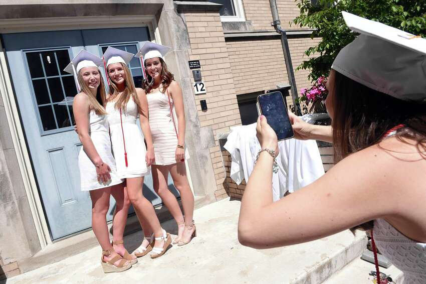 From left, Grace Plunkett, Stephanie Sullivan and Emily Ross have their photograph taken by Catherine Herrick before commencement in the Alumnae Courtyard at Sacred Heart Academy in Hamden on May 25, 2019.