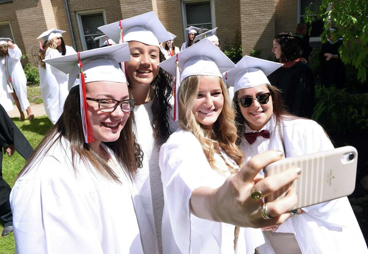 From left, Morgan McNabola, Judith Gonzalez, Zoe DeFalco and Kyleen Crowe take a selfie before commencement in the Alumnae Courtyard at Sacred Heart Academy in Hamden on May 25, 2019.
