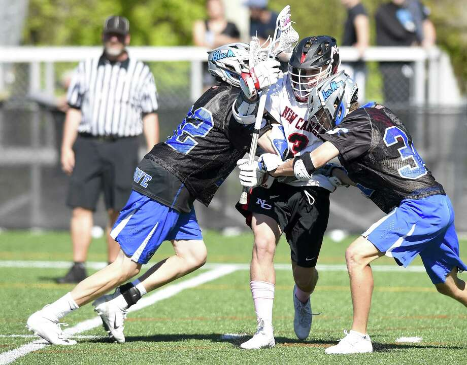 Darien's Jack Bogdan (32) and Tyler Strub (34) attempt to jam up New Canaan's Drew Guida on May 11. Photo: Matthew Brown / Hearst Connecticut Media / Stamford Advocate