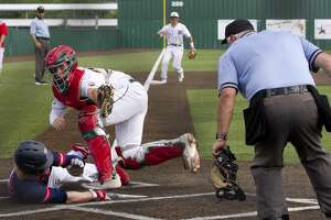 The Woodlands catcher Drew Romo (23) holds the ball up after making the tag on Dawson Goheen #12 of McKinney Boyd out in the fourth inning during a Game 3 of a Region II-6A semifinal high school baseball series at Corsicana High School, Saturday, May 25, 2019, in Corsicana.