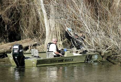 Texas game wardens remove an untagged and abandoned jug line and the catfish it captured from a tangle of willows along a public waterway. Abandoned jug lines, limb lines and trotlines take a toll on fish and other wildlife as well as posing issues for law enforcement and boating safety.