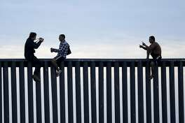 FILE - In this Nov. 21, 2018, file photo, two Honduran men pose as a photographer, at left, takes their picture after the group climbed the border wall separating Tijuana, Mexico, and San Diego, before climbing back down on the Mexican side, seen from San Diego. A federal judge is expected to decide Friday, May 24, 2019, whether to block the White House from spending billions of dollars to build a wall on the Mexican border with money secured under President Donald Trump's declaration of a national emergency. (AP Photo/Gregory Bull, File)
