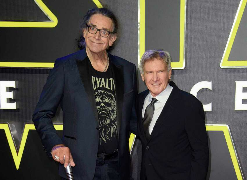 RETRANSMISSION TO CORRECT DAY AND DATE OF DEATH - FILE - This Dec. 16, 2015 file photo shows Peter Mayhew, left, and Harrison Ford at the European premiere of the film 'Star Wars: The Force Awakens ' in London. Mayhew, who played the rugged, beloved and furry Wookiee Chewbacca in the ?Star Wars? films, has died. Mayhew died at his home in north Texas on Tuesday, April 30, 2019 according to a family statement. He was 74. No cause was given. (Photo by Jonathan Short/Invision/AP, File)