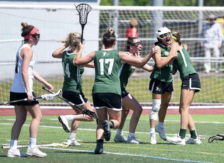 The Guilford girls lacrosse team celebrates with Catherine Larrow after Larrow scored the game-winning goal in overtime against Cheshire in the SCC championship game on Saturday. Photo: Dave Stewart / Hearst Connecticut Media / Hearst Connecticut Media