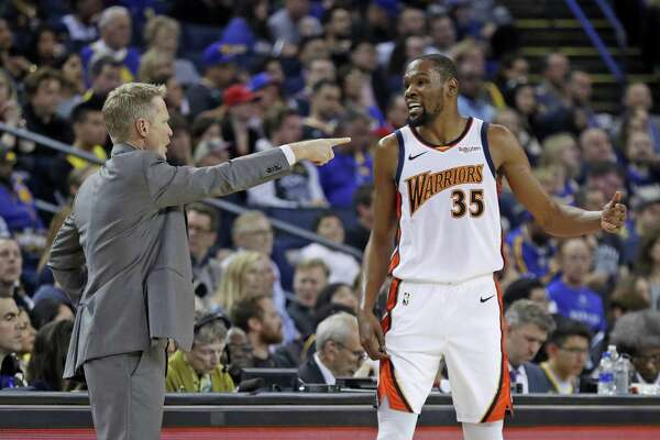 Golden State Warriors' head coach Steve Kerr confers with Kevin Durant in 2nd quarter against Los Angeles Clippers during NBA game at Oracle Arena in Oakland, Calif., on Sunday, April 7, 2019.