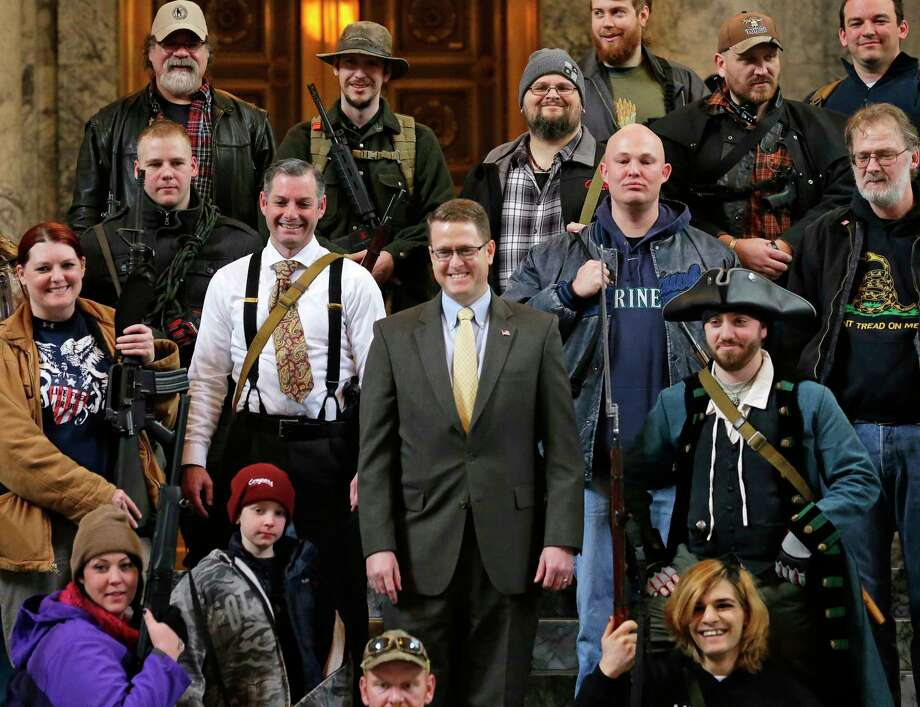 "FILE - In this Jan. 15, 2015, file photo, Washington Rep. Matt Shea, R-Spokane Valley, center, poses for a group photo with gun owners inside the Capitol in Olympia, Wash., following a gun-rights rally. Recently published internet chats from 2017 show Shea and three other men discussing confronting ""leftists"" with a variety of tactics, including violence, surveillance and intimidation. The messages prompted Washington House Democrats to demand that Shea be reprimanded for a history of far-right speech and activities. (AP Photo/Ted S. Warren, File) Photo: Ted S. Warren / Copyright 2019 The Associated Press. All rights reserved."