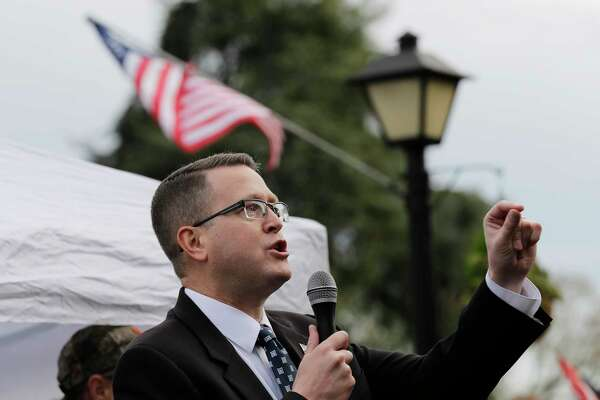 "FILE - In this Jan. 18, 2019, file photo, Rep. Matt Shea, R-Spokane Valley, speaks at a gun-rights rally at the Capitol in Olympia, Wash. Recently published internet chats from 2017 show Shea and three other men discussing confronting ""leftists"" with a variety of tactics, including violence, surveillance and intimidation. The messages prompted Washington House Democrats to demand that Shea be reprimanded for a history of far-right speech and activities. (AP Photo/Ted S. Warren, File)"