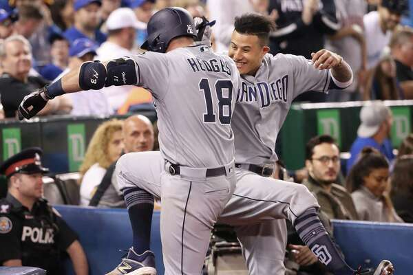 TORONTO, ON - MAY 25: Austin Hedges #18 of the San Diego Padres is congratulated by Manny Machado #13 after hitting a grand slam home run in the fourth inning during MLB game action against the Toronto Blue Jays at Rogers Centre on May 25, 2019 in Toronto, Canada. (Photo by Tom Szczerbowski/Getty Images)