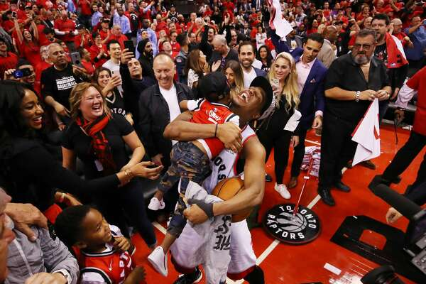 TORONTO, ONTARIO - MAY 25: Kyle Lowry #7 of the Toronto Raptors celebrates with his sons Kameron and Karter after defeating the Milwaukee Bucks 100-94 in game six of the NBA Eastern Conference Finals to advance to the 2019 NBA Finals at Scotiabank Arena on May 25, 2019 in Toronto, Canada. NOTE TO USER: User expressly acknowledges and agrees that, by downloading and or using this photograph, User is consenting to the terms and conditions of the Getty Images License Agreement. (Photo by Gregory Shamus/Getty Images)