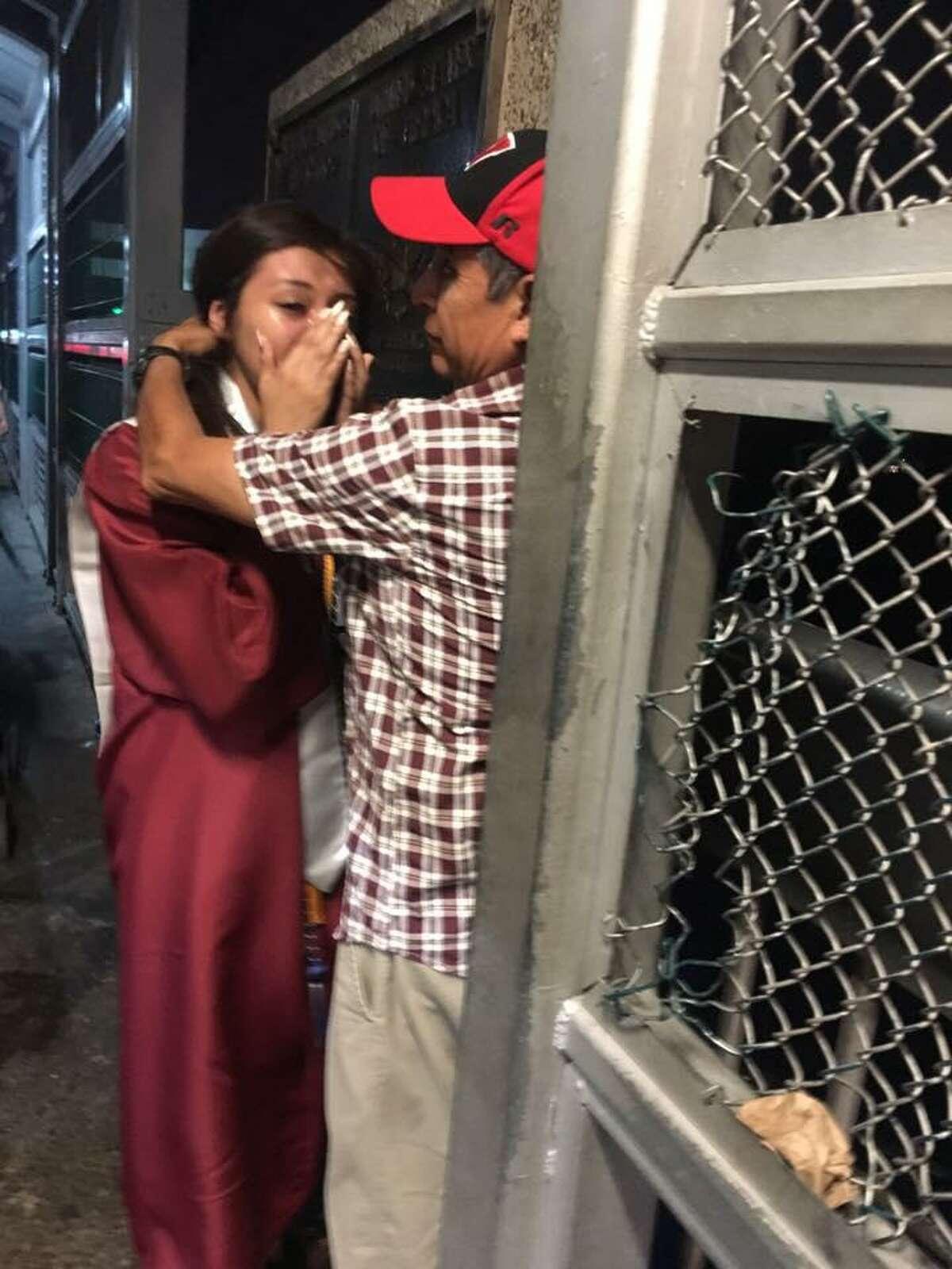 Saraí Ruiz se encuentra con su padre, Esteban Ruiz, a la mitad del puente después de asistir a su graduación de la preparatoria Héctor J. García Early College High School.