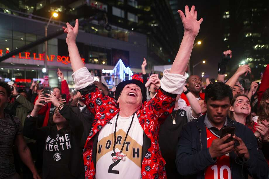 Toronto Raptors fans outside the arena celebrate in the closing seconds of the team's 100-94 win over the Milwaukee Bucks in Game 6 of the NBA basketball playoffs Eastern Conference finals Saturday, May 25, 2019, in Toronto. The Raptors won 100-94 to advance to the NBA Finals. (Chris Young/The Canadian Press via AP) Photo: Chris Young / Associated Press