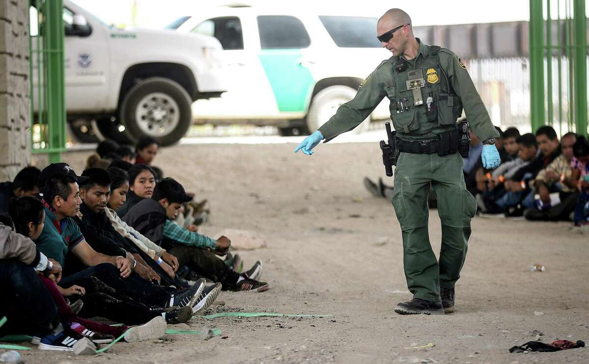 EL PASO, TX - MAY 19: A U.S. Border Patrol agent gestures towards migrants being detained after crossing to the U.S. side of the U.S.-Mexico border barrier, on May 19, 2019 in El Paso, Texas. The location is in an area where migrants frequently turn themselves in and ask for asylum after crossing the border. Approximately 1,000 migrants per day are being released by authorities in the El Paso sector of the U.S.-Mexico border amidst a surge in asylum seekers arriving at the Southern border. (Photo by Mario Tama/Getty Images)