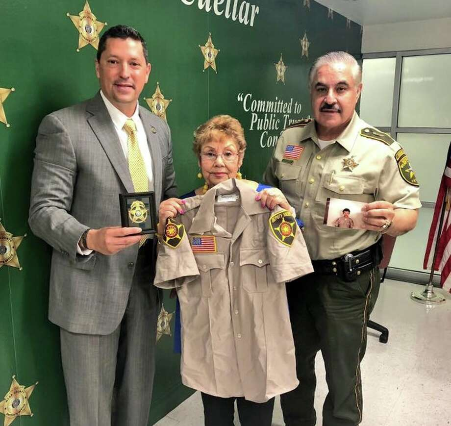 "District Attorney Isidro R. ""Chilo"" Alaniz and Sheriff Martin Cuellar present to Rosalinda Herrera the badge and uniform that belonged to her son and fallen officer Jose Gerardo ""Curly"" Herrera. Photo: Courtesy"