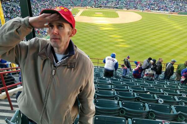 Stu Duncan salutes his late father, while wearing his father's Marine Corps hat, at a Texas Rangers game in Arlington. Benjamin, a retired 29-year veteran of the U.S. Marine Corps, died in January. Baseball was the pasttime shared by father and son.