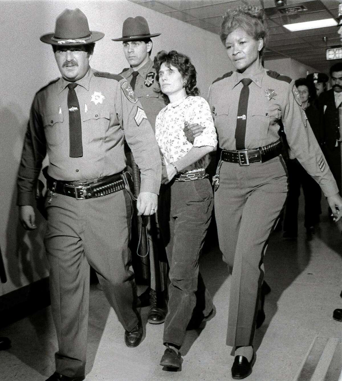 ** FILE ** Weather Underground member Katherine Boudin is led from Rockland County Courthouse in New City, New York, by sheriff's officers in this Nov. 21, 1981 file photo. Boudin learned her son, Chesa, had been named a Rhodes Scholar in a phone call to prison, where she has spent all but 14 months of his life. Chesa Boudin, a 22-year-old Yale senior and activist who speaks widely on the problems of children with incarcerated parents, was among the 32 American college students selected Sunday, Dec. 8,2002, for Rhodes scholarships. Boudin, the '60s radical who has served 22 years in prison for a 1981 armored car heist in which three men were killed, was granted parole Wednesday. She will be released prior to Oct. 1, 2003, from the Bedford Hills state prison in Westchester County, N.Y. (AP Photo/Handschuh, File) HOUCHRON CAPTION (08/21/2003): Officials did not explain the decision to parole Katherine Boudin, shown at her 1981 arrest.