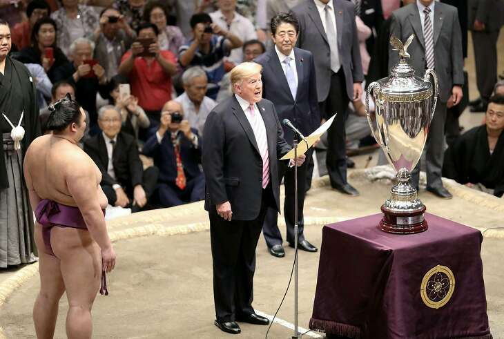 "President Donald Trump, center, speaks as Trump presents the ""President's Cup"" trophy to the Tokyo Grand Sumo Tournament winner Asanoyama, left, at Ryogoku Kokugikan Stadium, Sunday, May 26, 2019, in Tokyo. Japanese Prime Minister Shinzo Abe is at rear. (Kyodo News via AP)"
