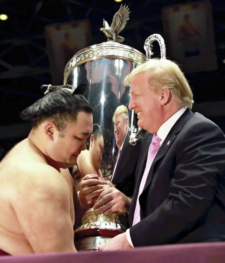 "President Donald Trump presents the ""President's Cup"" to Summer Grand Sumo Tournament winner Asanoyama in Tokyo on Sunday. Photo: The Japan News-Yomiuri / The Japan News-Yomiuri"