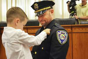 Middletown Mayor Dan Drew, Police Chief William McKenna, city hall employees, families and others attended Friday morning's officer promotion ceremony in council chambers. Here, Professional Standards Division Sgt. Brian Hubbs is pinned by his son.