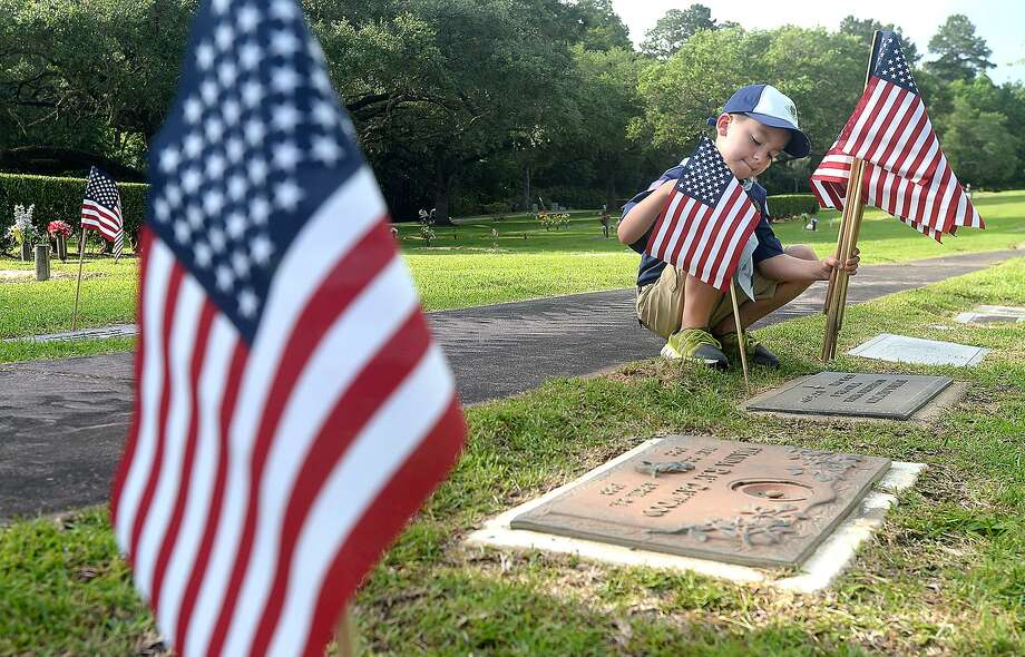 Cub Scout Pack 232 of Nederland member Hayden Gonzalez sets a flag in place as scouts, American Legion members and others prepare veterans' gravesites for Memorial Day at Forest Lawn Memorial Park Saturday.  Photo taken Saturday, May 25, 2019 Kim Brent/The Enterprise Photo: Kim Brent / The Enterprise / BEN