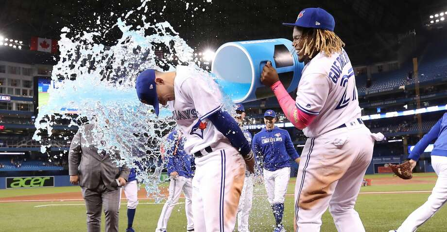 TORONTO, ON - MAY 26: Cavan Biggio #8 of the Toronto Blue Jays is doused by Vladimir Guerrero Jr. #27 following their victory over the San Diego Padres at the San Diego Padres at Rogers Centre on May 26, 2019 in Toronto, Canada. (Photo by Tom Szczerbowski/Getty Images) Photo: Tom Szczerbowski/Getty Images