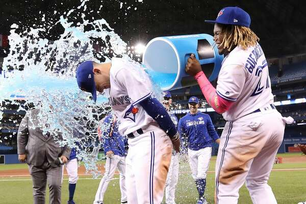 TORONTO, ON - MAY 26: Cavan Biggio #8 of the Toronto Blue Jays is doused by Vladimir Guerrero Jr. #27 following their victory over the San Diego Padres at the San Diego Padres at Rogers Centre on May 26, 2019 in Toronto, Canada. (Photo by Tom Szczerbowski/Getty Images)