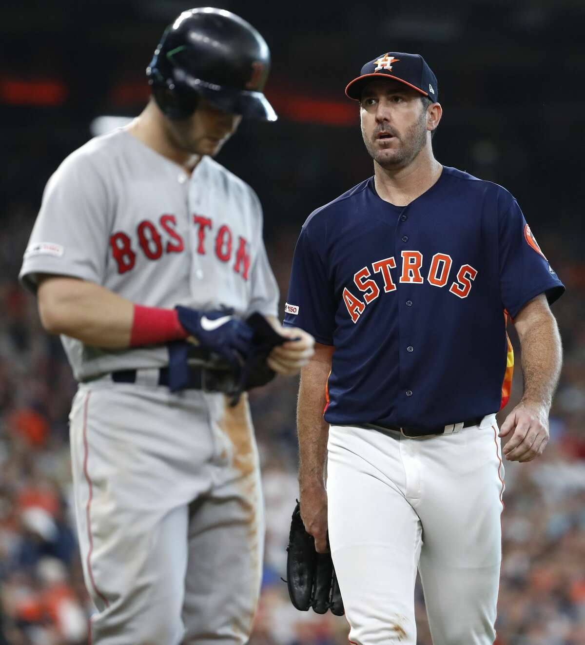 Houston Astros starting pitcher Justin Verlander walks past Boston Red Sox left fielder Andrew Benintendi at the end of the seventh inning of a major league baseball game at Minute Maid Park on Sunday, May 26, 2019, in Houston.
