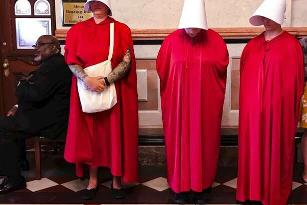 """Women dressed as Handmaids, characters from Margaret Atwood's dystopian novel, """"The Handmaid's Tale,"""" stand by as House Democrats meet on the other side of the door to discuss the future of the Reproductive Health Act on Wednesday at the Capitol in Springfield."""