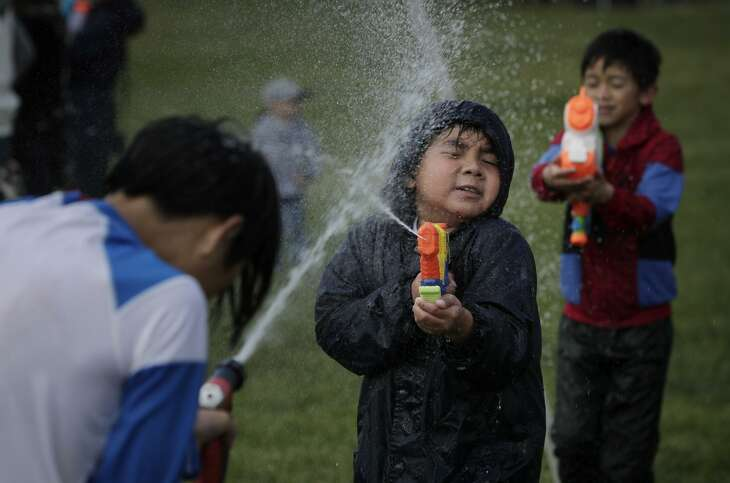 Silas Naing (left) and Jacob Ho blast each other with squirt guns during the Myanmar New Year Water Festival.