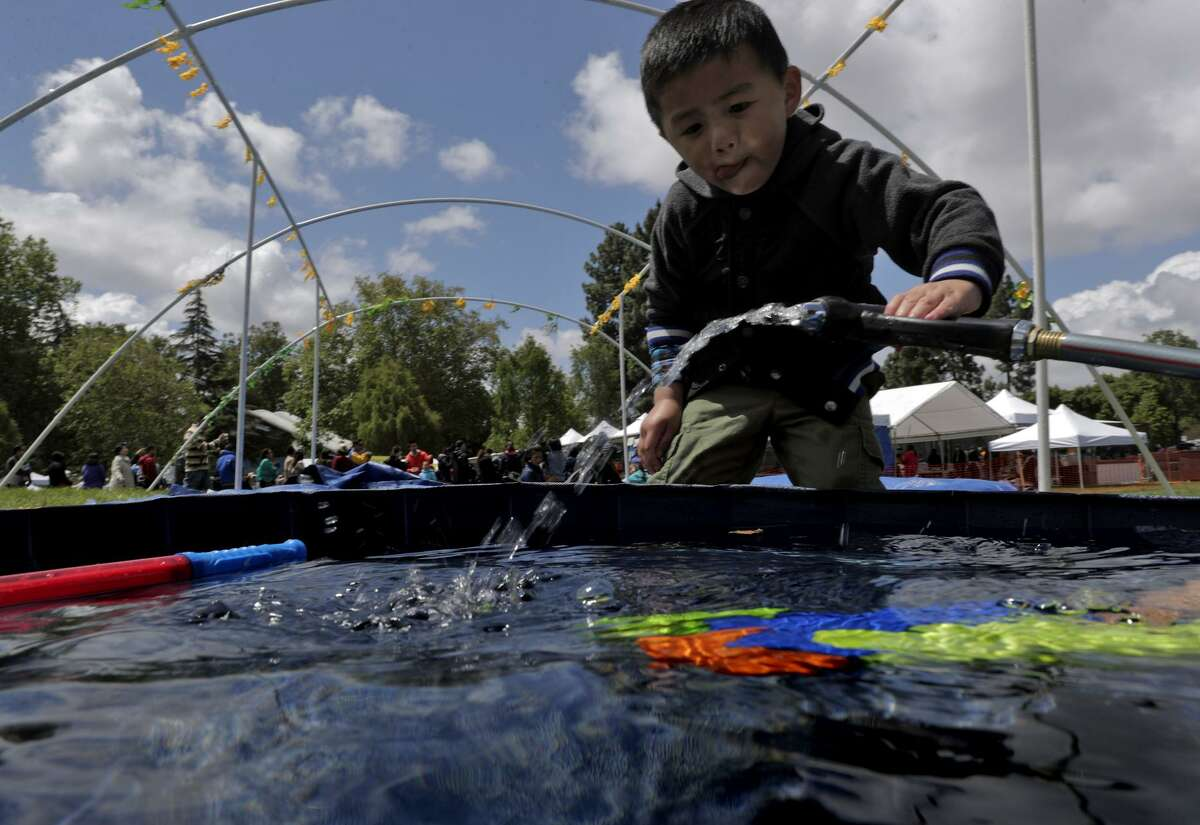 Three-year-old Leo Naing reaches for a hose to refill his squirt gun during the Myanmar New Year Water Festival at Kennedy Park in Union City. Water symbolizes washing away sins and starting fresh during the new year festivities.