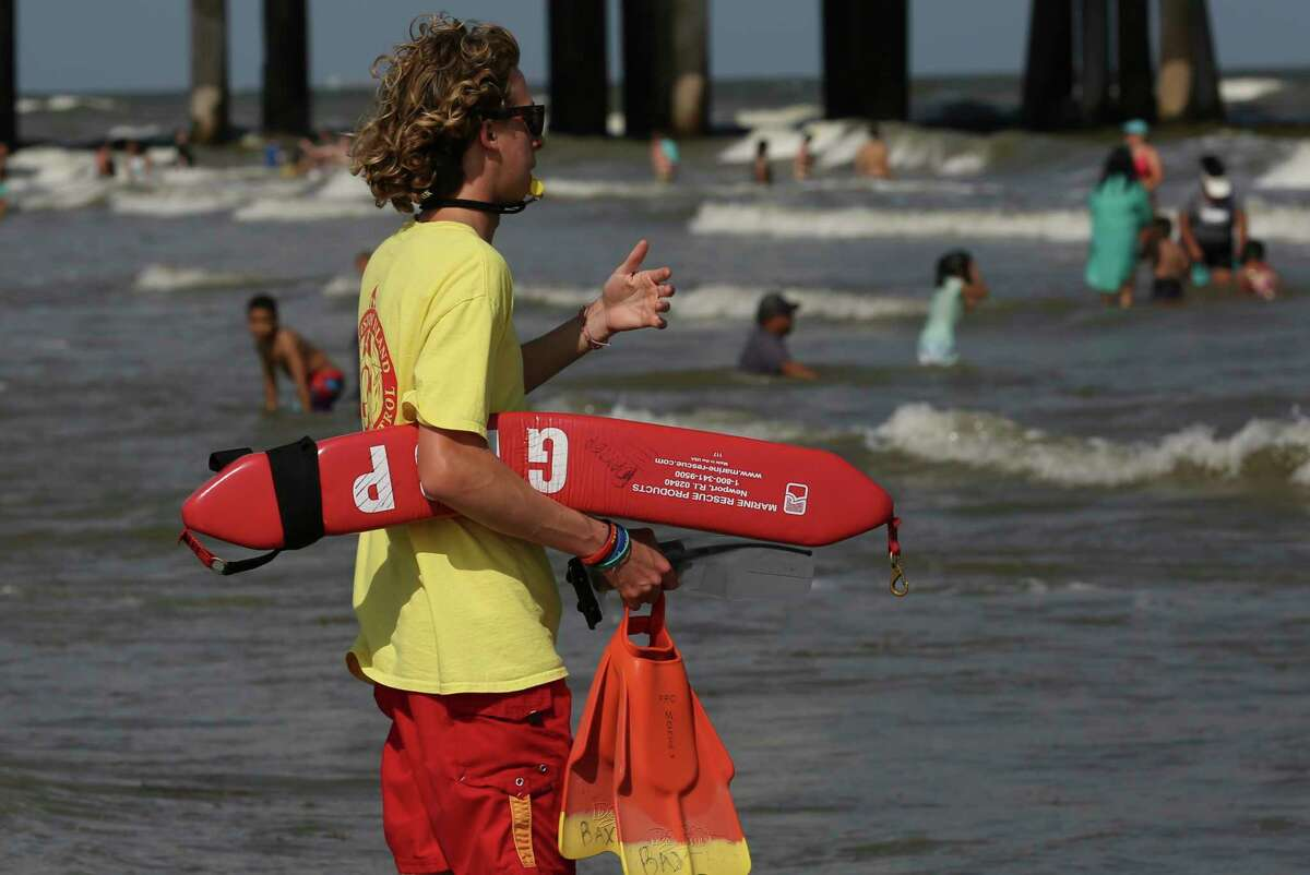 Lifeguard Baxter Wright calls swimmers away from the rip currents near Pleasure Pier on Sunday, May 26, 2019, in Galveston. A red flag warning was in place for strong rip currents at Galveston beaches on Sunday.