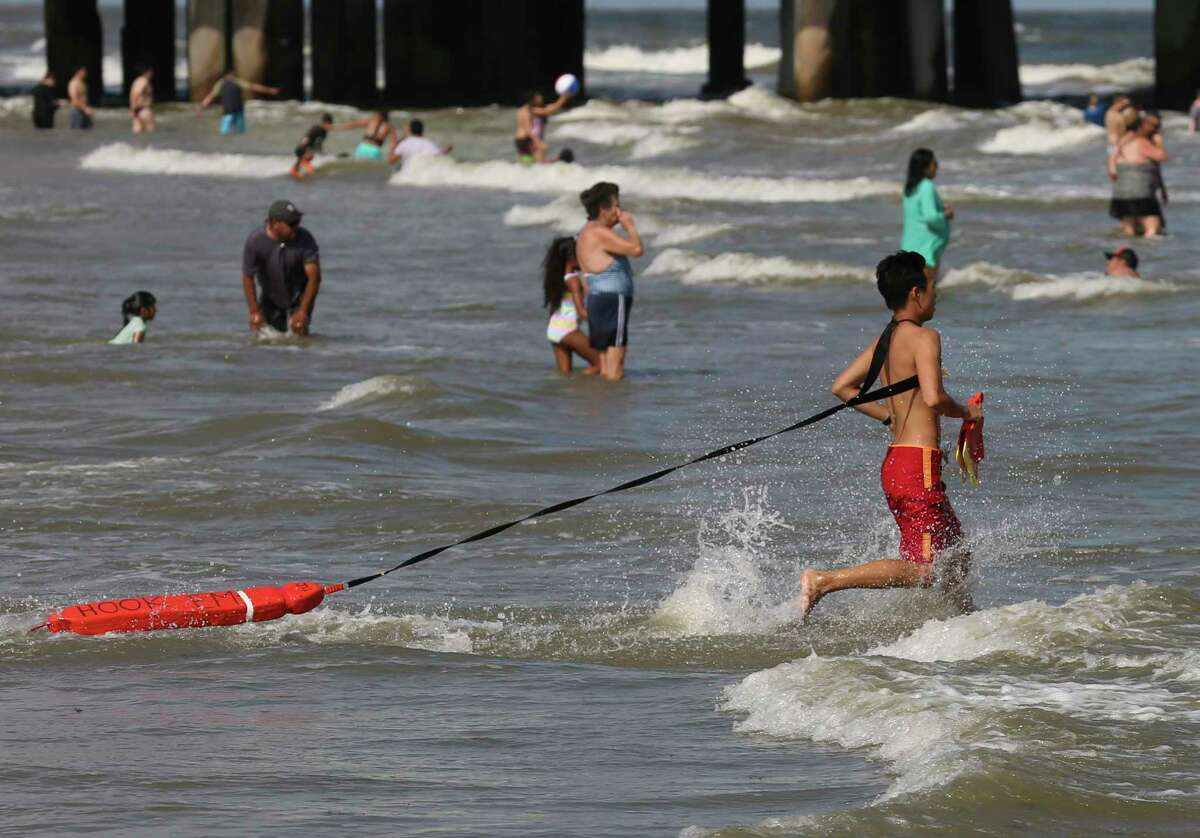 Lifeguard Jian Ju swims into the water to get swimmers away from the rip currents and come closer to the beach near Pleasure Pier on Sunday, May 26, 2019, in Galveston. A red flag warning was in place for strong rip currents at Galveston beaches on Sunday.