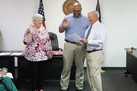 Debbie Beasley and Malcolm Goudeau are all smiles as Liberty mayor Carl Pickett swears the two board members into office on Tuesday, May 21. The two incumbents were re-elected to the board on May 4, 2019.