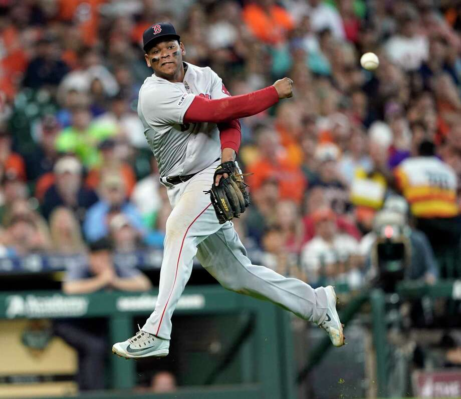 Boston Red Sox third baseman Rafael Devers throws to first for the out after fielding a ground ball off the bat of Houston Astros' Carlos Correa during the third inning of a baseball game Sunday, May 26, 2019, in Houston. (AP Photo/David J. Phillip) Photo: David J. Phillip / Copyright 2019 The Associated Press. All rights reserved