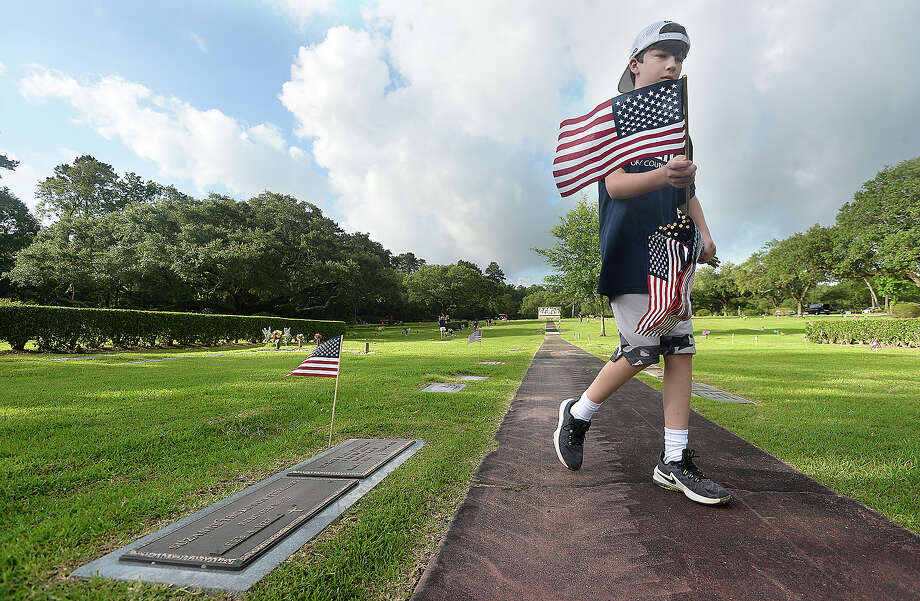 Taylor Neild makes his way through the cemetery as scouts, American Legion members and others prepare veterans' gravesites for Memorial Day at Forest Lawn Memorial Park Saturday.  Photo taken Saturday, May 25, 2019 Kim Brent/The Enterprise Photo: Kim Brent/The Enterprise