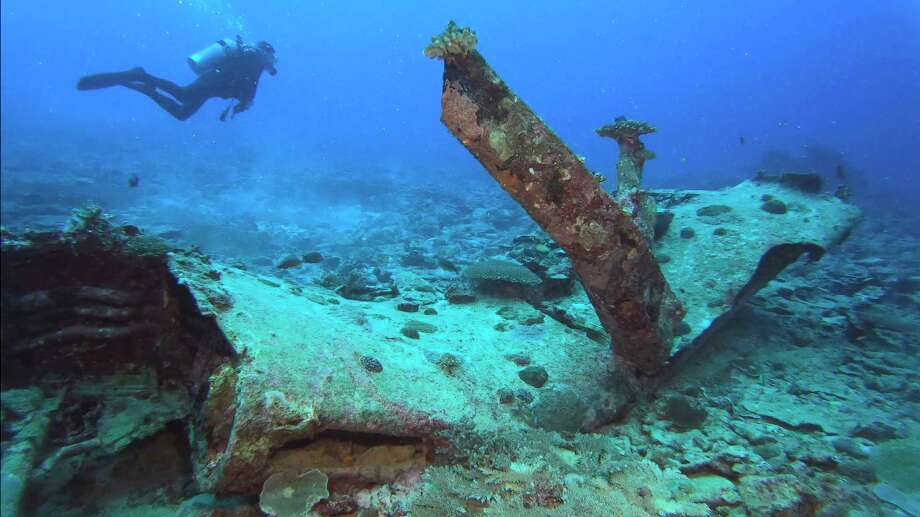 In this March 24, 2019 photo provided by Justin Taylan of PacificWrecks.com, a scuba diver swims near the left wing wreckage of an F4U-4 Corsair fighter aircraft off Sonai, Iriomote Jima, in Japan. World War II researcher Justin Taylan says the airplane wreckage on the ocean floor near Okinawa is from the fighter-bomber flown by John McGrath, a U.S. pilot from New York who's still listed as missing in action. (Justin Taylan via AP) Photo: Justin Taylan/PacificWrecks.com / Justin Taylan