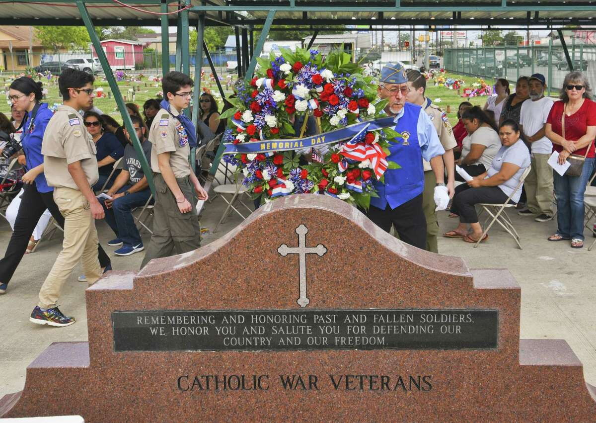 A Memorial Day wreath is moved toward the flag pole on Saturday during the Calvary Catholic Cemetery Memorial Day Mass.